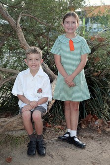 Boy sitting down on tree wearing grey shorts and white short sleeved shirt, girl standing wears the light green summer tunic dress.