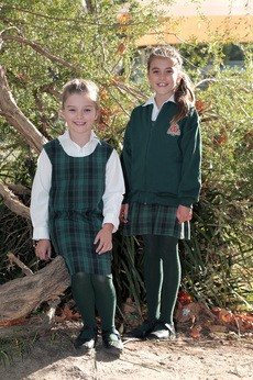Two girls in the winter uniform, wearing the tunic dress with long sleeved white shirt and green tights. One is also wearing a school fleece jacket.
